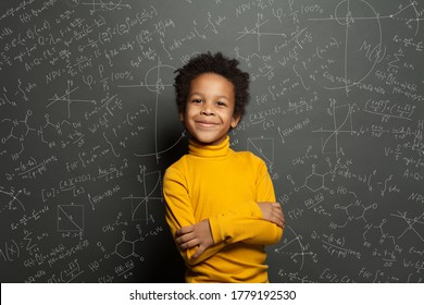 Smart African American child student boy on chalkboard background with science formulas