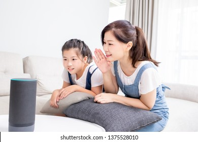 Smart AI speaker concept - Mom and daughter talk to voice assistant at home and feel happy