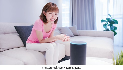Smart AI speaker concept - Young Woman talk to voice assistant at home and feel happy