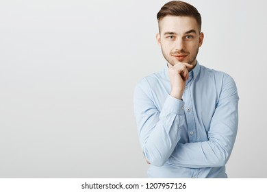 Smart ambitious handsome male in trendy blue collar shirt holding hand on chin smirking from interest and delight gazing at camera intrigued while listening to interesting idea, being boss