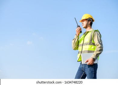 smart asian adult male engineer wearing safety vest and hardhat standing holding laptop and walkie talkie, outdoor with clear blue sky background. site worker concept.