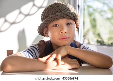 smart asian boy with knitted wool hat sitting near window and thinking about something