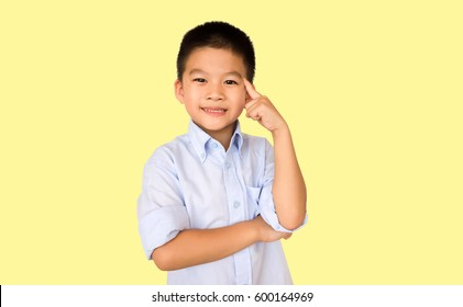 Smart asian boy in thinking act isolated on yellow background.