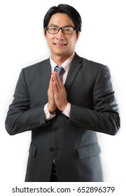 "Smart asian business man gesturing ""Wai"" or ""Sawasdee"" Thai greeting isolated on white background"