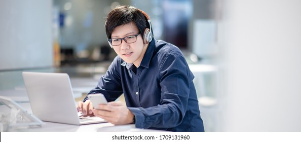 Smart Asian businessman in casual clothing using smartphone and laptop computer working at home office. Male manager using mobile app for social media and online news. Technology for business strategy