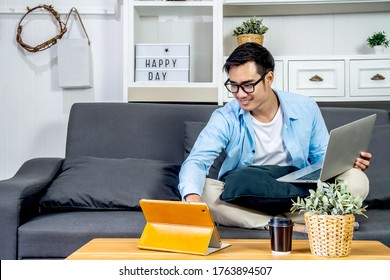 Smart Asian businessman in casual clothing sitting on a sofa in the house is working on computer laptop and tablet , SME start up concept, work from home