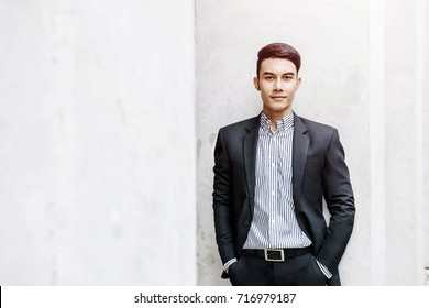 Smart Asian Businessman in Formal Suit, Looking at Camera and Smiling in Outside Building