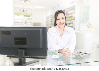 smart asian female pharmacist rest in drugstore, she feeling happy and smile, she rest arm on glass counter