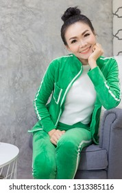 smart asian femalerelax on gray sofa, she sitting and smile, she rest chin on her hand, she wear green costume and feeling confident