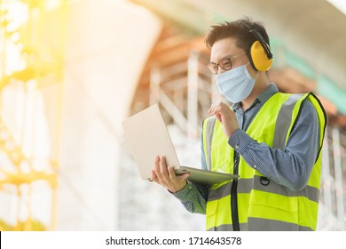 smartes asiatisches Männchen mit Schutzmaske, professioneller Bauingenieur, tragbarer Laptop-Baukasten mit Infrastruktur und Bauhintergrund
