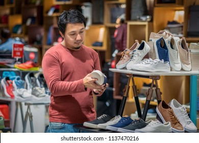 Smart asian man with beard choosing fashion shoes in store shop at department shopping center, beauty and Consumerism Concept.