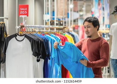Smart asian man with beard choosing clothes in clothing store at shopping center, looking t-shirts sale 20% off, Fashion and Consumerism Concept.