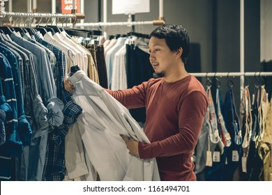 Smart asian man with beard choosing clothes in clothing store at shopping center, looking white color t-shirts , Fashion and Consumerism Concept.