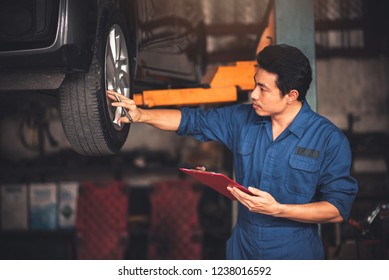 Smart Asian Man Mechanic Auto Service Shop Owner in Blue Uniform are Holding Clipboard Car Checklist for Working with Smiling in Automobile Garage