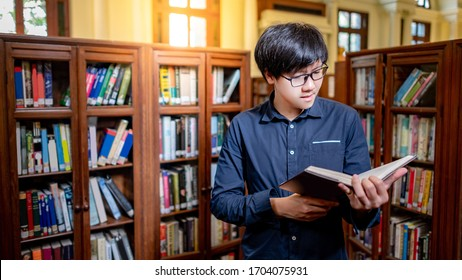 Smart Asian man university student wearing glasses reading book by vintage bookshelf. Textbook resources in college library for educational subject and research. Scholarship for education opportunity.