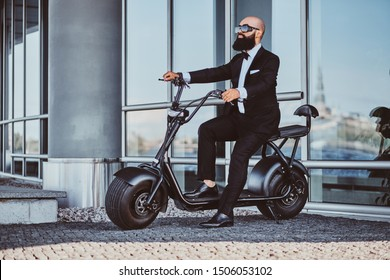 Smart attractive businessman is sitting on his electro scooter while posing for photographer.