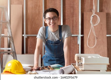smart attractive handy glasses asian male craftman or interior designer focus wood working at site constrution home interior design house renovation and improvement concept