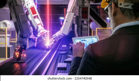 Smart automation industry robot in action welding metall while engineer uses his remote control table pc- industry 4.0 concept
