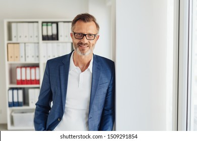 Smart bearded businessman wearing glasses leaning against a wall alongside glass exterior door in the office smiling at the camera