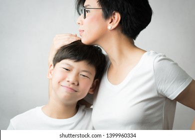 A smart and beautiful asian mom holding her preteen son with love. Her son leans his head on her chest smiling happily. Love expression, Parenting teen, Single mom, Young son, Mommy's love Concept.