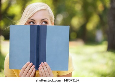 Smart beauty. Beautiful young women holding book in front of her face and looking out of it while relaxing in park