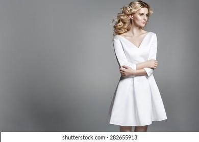 Smart blond lady wearing white dress