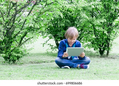 Smart boy sitting with tablet computer outdoors