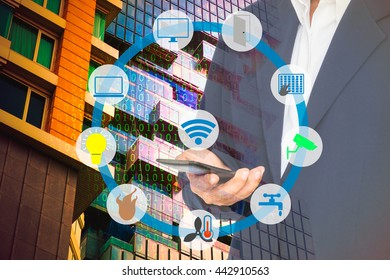 Smart building and internet of things technology concept. Smart building wireless network against double exposure of business man using smartphone and building with abstract binary code background.