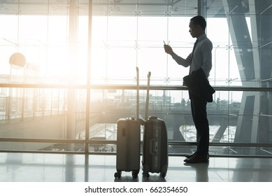 Smart business man standing  in the international  airport 2 luggages beside him looking at telephone hand holding  connecting business on line during waiting flight departure,business and technology