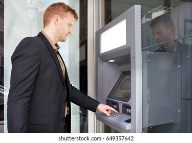 Smart business man using cash machine to withdraw cash at bank, slick office building. Professional elegant male dialing keys at cash point, money banking services, using credit card. Business people.