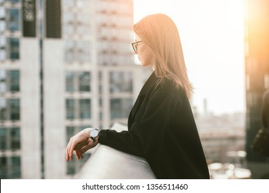 Smart business woman in glasses thinking about business strategy standing on the city office rooftop at sunset time