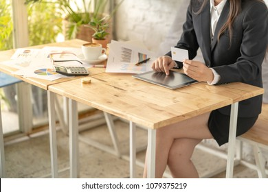 Smart business woman hand holding a smartcard and working on tablet. Concept for home office or cozy work space