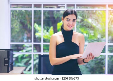 Smart business woman using laptop/notebook to record or update her job which assign from boss or management. Standing at office workplace in her personnel working room with smiley face and happiness