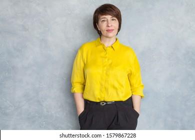 Smart business woman wearing yellow shirt. Mature woman 45 years old