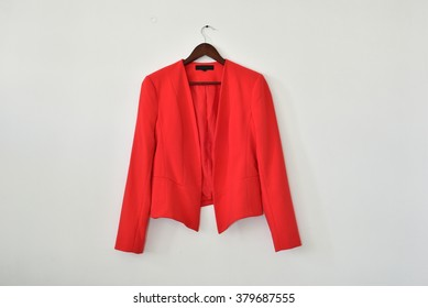 Smart business women's blazer on a hanger isolated on white wall background, with lot of empty space for text