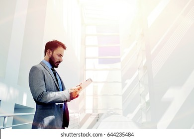 Smart businessman dressed in luxury suit holding touch pad while standing in modern office space with big copy space area for your text message, young intelligent male using digital tablet for work