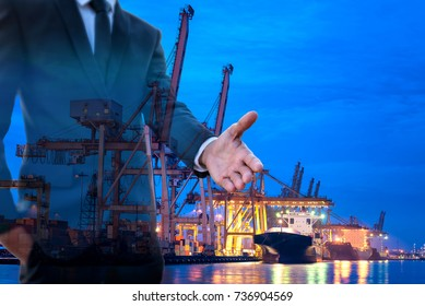 Smart businessman hand, Investment business Invitation with transportation ship and crane import export at port in the twilight morning background