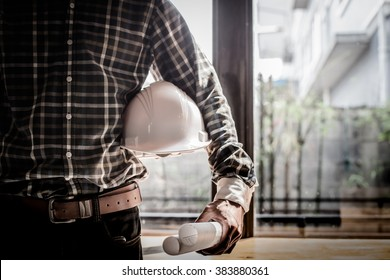 Smart Businessman holding construction helmet and blueprints in retro style.