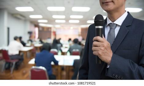 Smart businessman, manager having speech in business seminar. Teacher holding microphone teaching student in university auditorium.