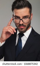 smart businessman placing finger on glasses thinking about something on grey background