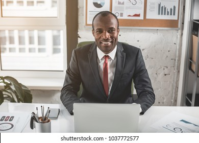 Smart businessman. Portrait of cheerful young successful african businessman in formal wear is sitting at table in modern office and working on laptop. He is looking at camera with joy