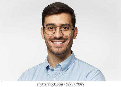 Smart businessman smiling at camera, wearing round glasses, isolated on gray background