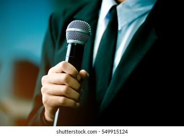Smart businessman speech speaking present in seminar, talking with microphone keynote in convention or conference hall. Startup Business speaker teaching to audience in university classroom