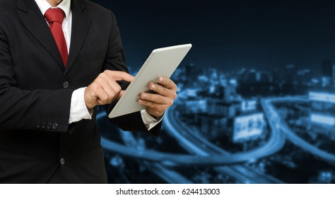 smart businessman in suit using his tablet, business and technology concept on blurred night city background,copy space, color tone effect.