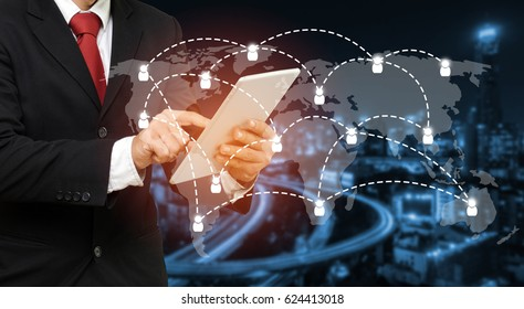 smart businessman in suit using his tablet, business and technology concept with world map social media network connection on blurred night city background, color tone effect, wide screen.