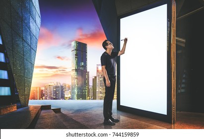 Smart businessman writing on big and blank white screen with modern city skyline background .
