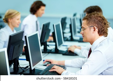 Smart businesspeople typing at workplaces in computer room