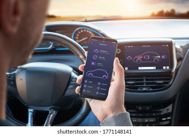 Smart Car app with engine, tyres and battery status information concept. Driver holds a mobile phone. Steering wheel and board display in the background