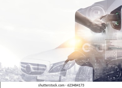 Smart car , Electric vehicle charging home station technology concept. Double exposure of Hand charging an electric car (EV) with the power cable supply plugged in and luxury car. Flare light effect