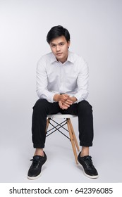 Smart casual asian man seated on chair, posing while looking at camera in studio background